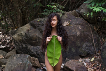 Beautiful naked young woman in jungle with palm leaf