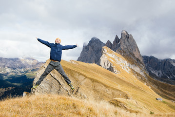 Man tourist jumping with happiness on a background of mountains. Dolomite, Alps