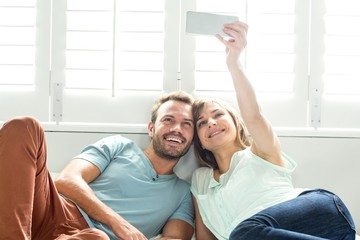Couple taking selfie while relaxing on bed