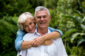 Senior woman embracing husband from behind against plants