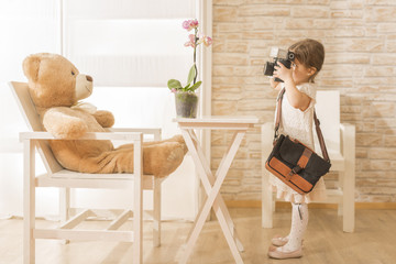 A little child photographer is taking a photo to her teddy bear. Art or creativity concept. Young girl holding old vintage film photo camera and taking pictures, horizontal photo