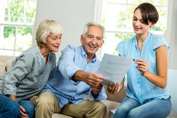 Smiling female consultant showing report to senior couple