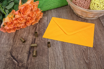 Envelope, tulips and bullets on a wooden background
