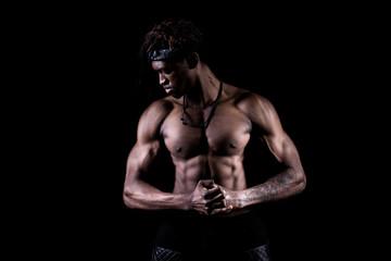Studio shot of muscular afroamerican man posing with black background