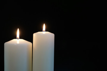 burning candles isolated on black background.