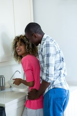 Man embracing woman while washing dishes