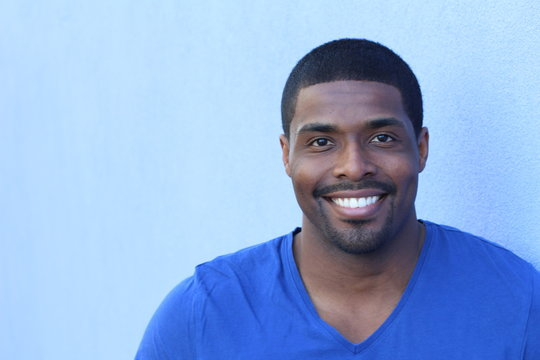 Close up portrait of a happy black man in his 20s with a perfect smile isolated on a blue background with copy space