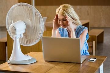Tense woman sitting in desk
