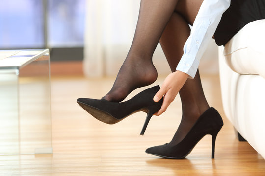 Businesswoman taking off shoes
