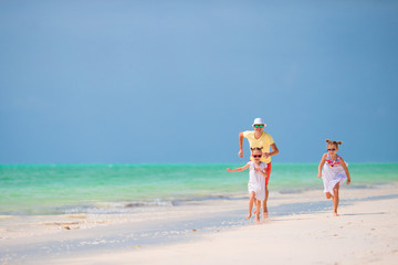 Happy father and his adorable little daughters at tropical beach