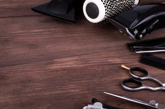 Professional hairdressing equipment on a dark wooden background. Tools for hairdresser, beauty salon.