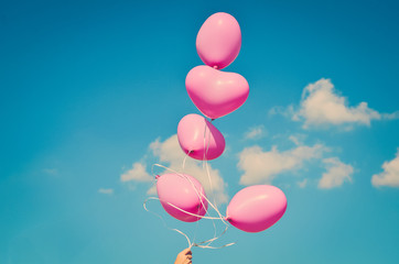 Pink balloons in the shape of hearts rise up into the sky with clouds (vintage)