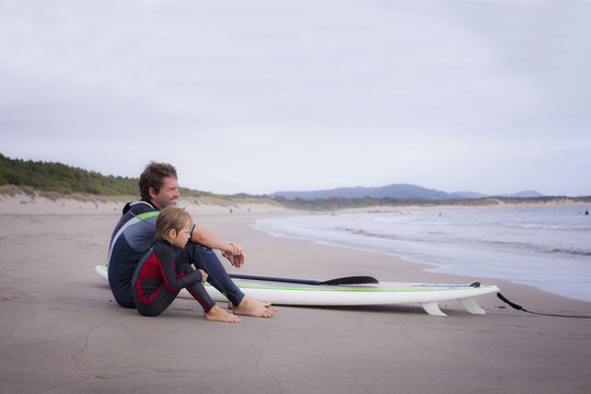 Father and son sitting on beach with paddleboard