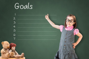Cute little girl wearing business dress and showing blank goal list on green chalk board.