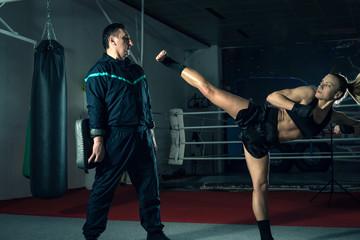 Girl kicking back leg during kickboxing practice