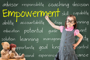 Cute little girl wearing business dress and showing empowerment concept on green chalk board.