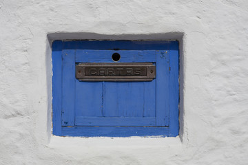 "old, wooden, blue painted letter box in a white wall in Sitges, Spain, ""Carta"" is letter in Spanish"