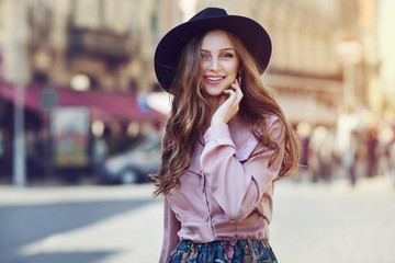 Outdoor portrait of young beautiful fashionable happy lady posing on a street of the old city. Model wearing stylish wide-brimmed hat & clothes. Girl looking at camera. Female fashion. City lifestyle
