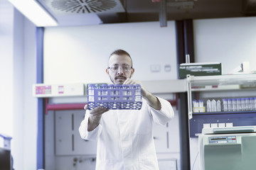 Young scientist arranging test tubes in test tube rack at pharmacy laboratory, Freiburg im Breisgau, Baden-Württemberg, Germany