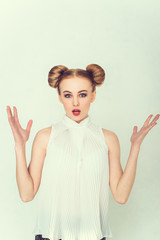 Portrait of surprised beautiful girl with funny hairstyle with open hand and open-mouthed.