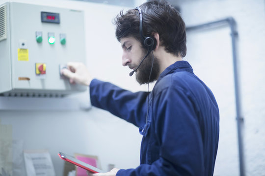 Young male engineer wearing headset and updating control panel using digital tablet in an industrial plant, Freiburg im Breisgau, Baden-Württemberg, Germany