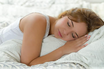 Young brunette woman in bed, comfortably asleep on white sheets and pillow with eyes closed