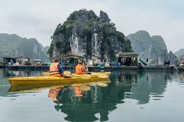 Couple rowing kayak, photographing sea in Halong Bay.