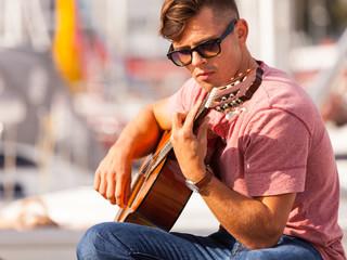 Young man playing guitar.