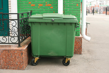 Dumpster next to the house. Ecological concept.