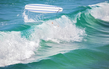 Surfer legs in water and surfing board in the air after falling a wave.