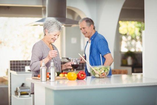 Cheerful senior couple at kitchen counter