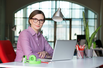 Smiling Business Lady in casual clothing sitting at Office Table