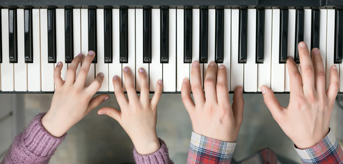 Piano Keyboard top View and Hands of Child and Mother