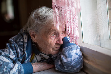 An elderly woman sadly looking out the window.