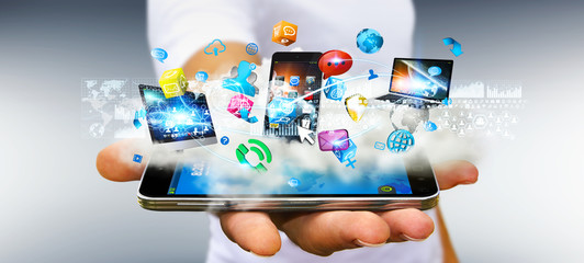 Businessman holding tech devices and icons applications over a c