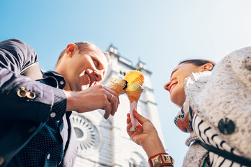 Couple in love with ice-cream cones on San Lorenco Cathedral bac