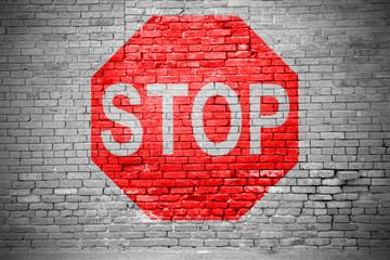Ziegelsteinmauer mit Stoppschild Graffiti
