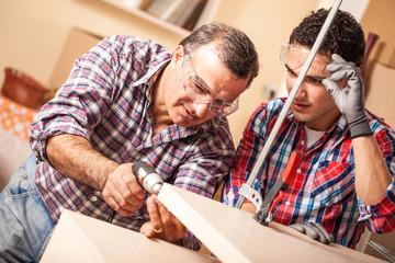 Two carpenters working at location.Repairing furniture.
