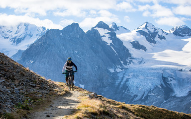 Woman on mountain bike woodland trail, South Tyrol, Italy