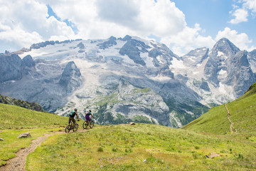 Man and woman riding mountain bikes along trail, Dolomites, Italy