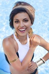 Beautiful woman near the pool wearing colored turban