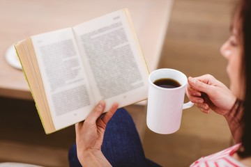 Cropped image of woman reading book while holding coffee cup