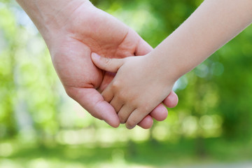 Father holds hand of the child against beautiful bokeh background in sunny day, happy family concept, shallow dof
