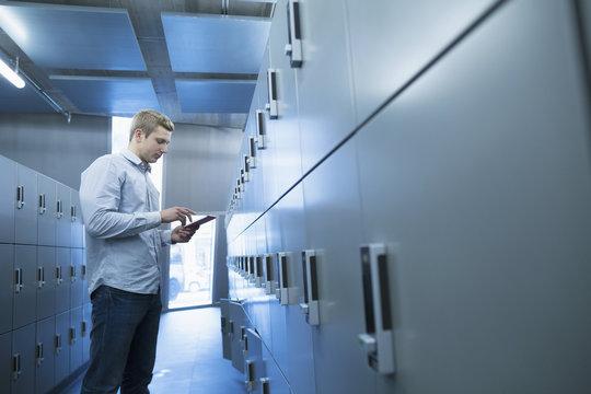 Young university student using digital tablet in locker room, Freiburg im Breisgau, Baden-Württemberg, Germany