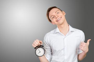 Young businessman keeping clock