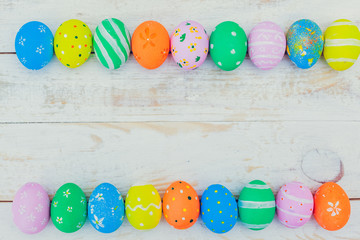 Easter eggs painted in pastel colors on white wooden background.