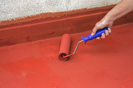 Hand painting a red floor with a paint roller