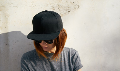 Portrait of a young attractive girl with cap.Female model wearing a black blank cap and sunglasses looking away.
