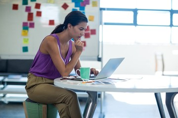 Young woman sitting at desk using laptop