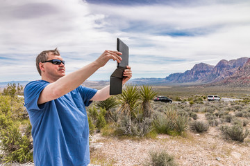 Man taking picture using tablet computer in mountains valley